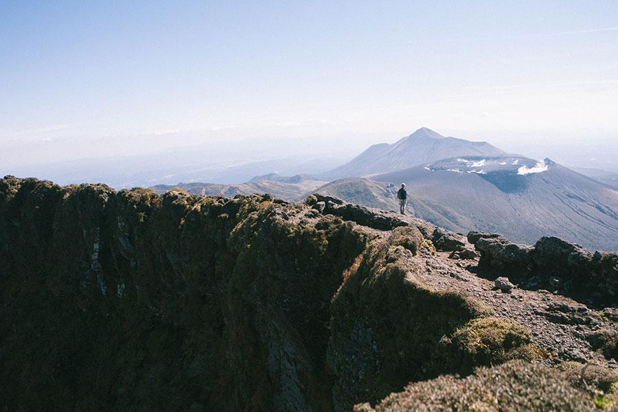 韓国岳の爆裂火口と新燃岳と高千穂峰を眺めるご紳士