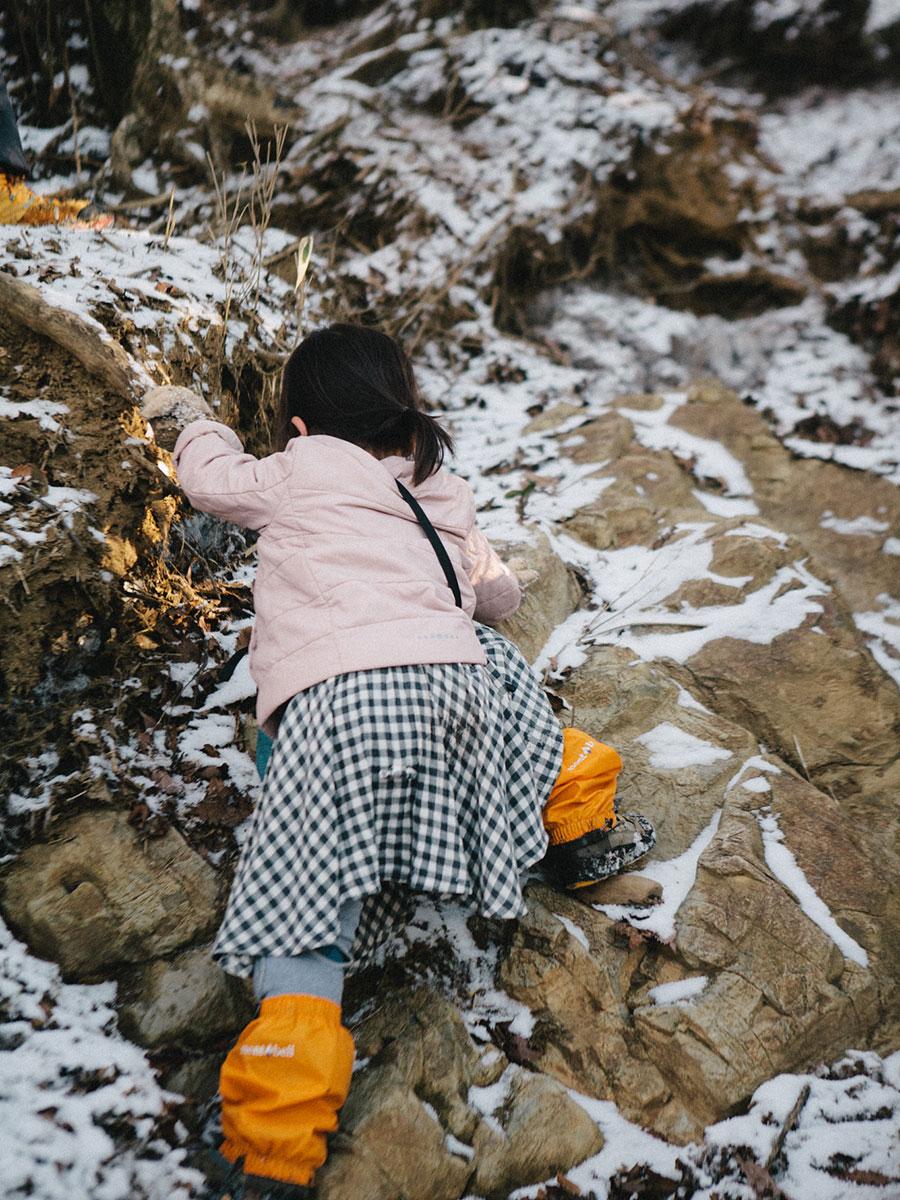 雪混じりの岩場を攀じ登る娘