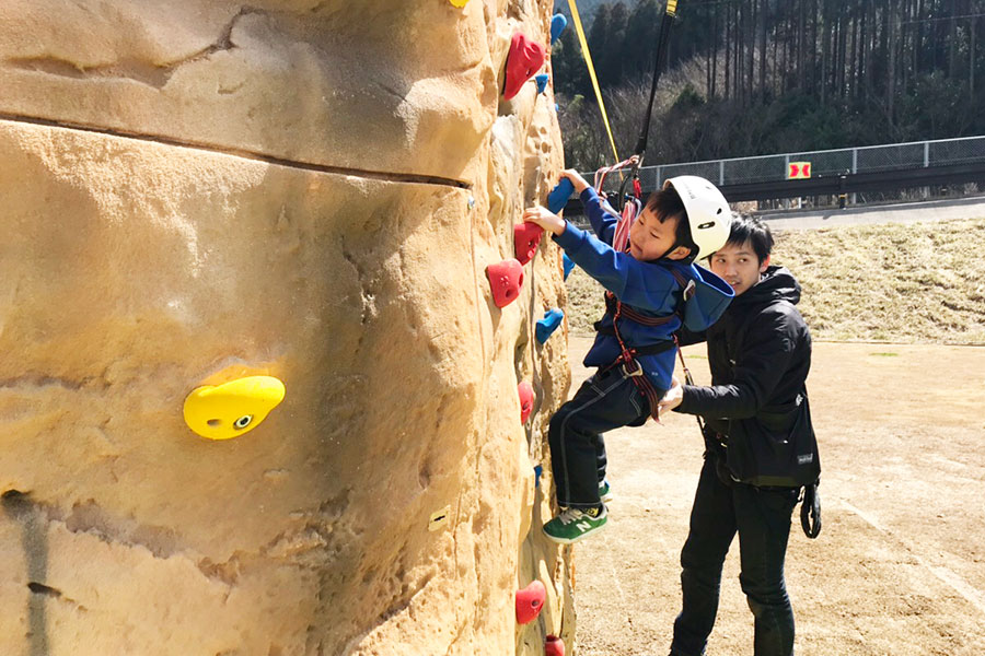 クライミングウォールをよじ登る4歳児